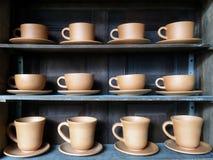 Ретро чашки глины Брайна для горячих кофе или чая в строке на полке Стоковые Фотографии RF