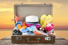 Ретро чемодан с объектами перемещения на деревянном Стоковые Изображения