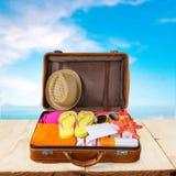 Ретро чемодан с объектами перемещения на пляже Стоковое Фото