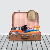 Ретро чемодан с объектами перемещения на предпосылке Стоковые Изображения