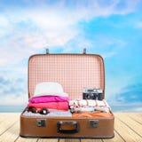 Ретро чемодан с объектами перемещения на предпосылке Стоковые Фотографии RF