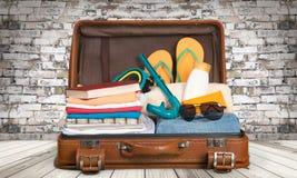 Ретро чемодан с объектами перемещения на предпосылке Стоковое Фото