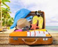 Ретро чемодан с объектами перемещения на тропическом Стоковая Фотография