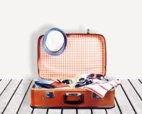 Ретро чемодан с перемещением возражает на деревянной доске Стоковые Фото