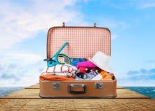 Ретро чемодан с перемещением возражает на деревянной доске Стоковое фото RF