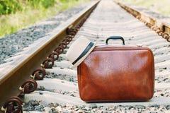 Ретро чемодан стоя на железной дороге на солнечный день Праздники, каникулы, перемещение и отключение Стоковое фото RF