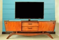 Ретро шкаф телевидения в комнате против голубой стены Стоковая Фотография