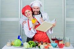 Рецепты книги Полезная кулинарная книга Шеф-повар и человек женщины варя еду совместно Кулинарная концепция семьи E стоковое фото rf