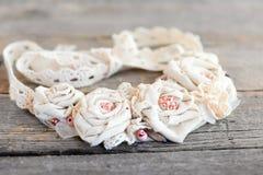 Рециркулированное ожерелье ткани от отделок шнурка, шариков и основания войлока изолированного на винтажной деревянной предпосылк Стоковые Фото