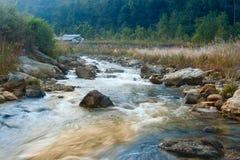 Речная вода пропуская через утесы на зоре Стоковые Фото