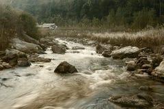 Речная вода пропуская через утесы на зоре Стоковое Изображение