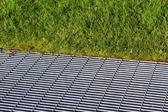 Решетка металла на том основании в зеленой траве Стоковое Изображение RF