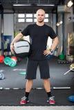 Решительно мужской спортсмен держа шарик медицины в оздоровительном клубе стоковое фото rf