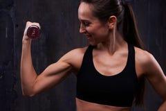 Решительно женщина во время упорно добиваться тренировка в темной студии стоковое фото