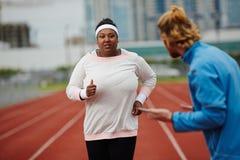 Решительно женщина плюс-размера бежать на следе Стоковая Фотография RF