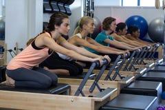 Решительно женщины практикуя протягивающ тренировку на реформаторе Стоковое Фото