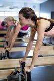 Решительно женщины практикуя протягивающ тренировку на реформаторе Стоковая Фотография