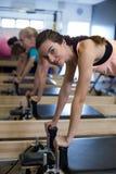 Решительно женщины практикуя протягивающ тренировку на реформаторе Стоковые Фото
