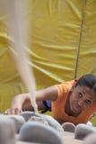 Решительно молодая женщина взбираясь вверх взбираясь стена в крытом взбираясь спортзале, сразу выше Стоковое Изображение