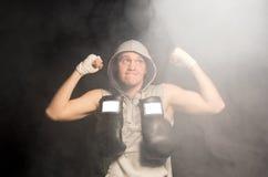 Решительно молодой боксер поднимая его кулаки стоковая фотография rf