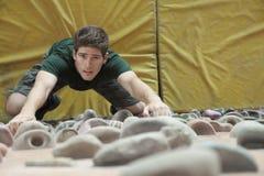 Решительно молодой человек взбираясь вверх взбираясь стена в крытом взбираясь спортзале, сразу выше Стоковые Изображения RF