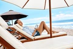 Релаксация лета Чтение женщины, ослабляя на пляже Летнее время Стоковое Изображение