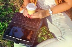 Релаксация с чашкой кофе и таблеткой Девушка с компьтер-книжкой кофе Красивая молодая женщина при тетрадь сидя на траве Стоковая Фотография