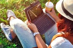 Релаксация с чашкой кофе и таблеткой Девушка с компьтер-книжкой кофе Красивая молодая женщина при тетрадь сидя на траве Стоковые Фото