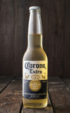 Редакционное фото бутылки пива короны дополнительного на темной деревянной предпосылке Стоковое Изображение