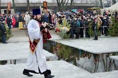Религиозное христианское пиршество явления божества. Священник, епископ благословляет воду и людей Стоковое фото RF
