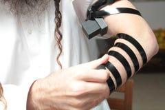 Религиозный правоверный еврей с рукой-tefillin на его левой руке молит a еврейский человек подготавливает tefillin Стоковое Фото