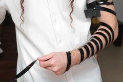 Религиозный правоверный еврей с рукой-tefillin на его левой руке молит a еврейский человек подготавливает tefillin Стоковые Изображения RF