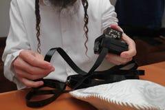 Религиозный правоверный еврей с рукой-tefillin на его левой руке молит a еврейский человек подготавливает tefillin Стоковое Изображение