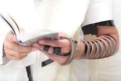 Религиозный правоверный еврей с рукой-tefillin на его левой руке молит a еврейский человек подготавливает tefillin Стоковые Изображения
