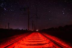 Рельсы против звёздного неба с необыкновенным красным освещением Стоковое Изображение