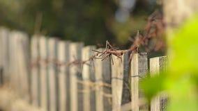 Ржавая колючая проволока на старой деревянной загородке акции видеоматериалы