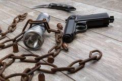 Ржавая цепь с ложью пистолета на деревянной предпосылке Стоковые Фотографии RF