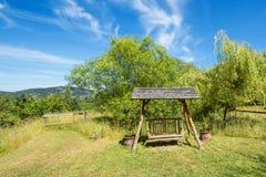 Ржавея стенд качания в пышном саде Стоковая Фотография