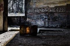 Ржавые бочонок и надписи на стенах в промышленных руинах Стоковые Изображения