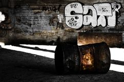 Ржавые бочонок и надписи на стенах в промышленных руинах Стоковое фото RF