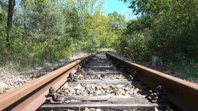 Ржавые получившиеся отказ железнодорожные пути в лесе все еще сняли с движением ветра в деревьях Перемещение, конец мира или один акции видеоматериалы