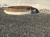 Ржавый железный люк -лаз установил в дорожные покрытия асфальта Стоковое Изображение RF