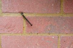 Ржавый изогнутый ноготь в красной кирпичной стене стоковое изображение