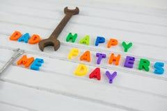 Ржавый ключ multi покрашенным счастливым текстом дня отцов на таблице Стоковые Фотографии RF