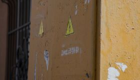 Ржавый муниципальный электрический серый внешний шкаф с замком и знак опасности изолированный на белизне Стоковое фото RF