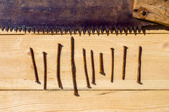 Ржавый увидел и 10 ногтей на деревянном столе Стоковые Фотографии RF