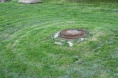 Ржавый люк -лаз на лужайке накошенной в кругах Стоковое Изображение