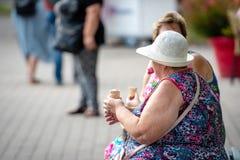 РИГА, ЛАТВИЯ - 18-ОЕ АВГУСТА 2018: 2 старухи сидят на стенде и едят мороженое стоковое фото rf