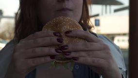 РИГА, ЛАТВИЯ - 22-ОЕ АПРЕЛЯ 2019: Конец гамбургера вверх по - молодая женщина есть в ресторане Mcdonalds фаст-фуда - большому Mac видеоматериал