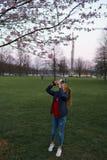 РИГА, ЛАТВИЯ - 24-ОЕ АПРЕЛЯ 2019: Люди в парке победы наслаждаясь вишневым цветом Сакуры - каналом города с летанием чайок стоковые изображения